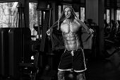 Portrait Of A Physically Fit Man In Hoodie - In Modern Fitness Center - Showing His Six Pack - Black And White Photo poster