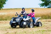 Couple driving off-road with quad bike or ATV poster