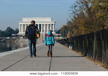 Washington DC - December 6 2015: A man and child seen walking along the reflection pool headed toward the Lincoln Memorial