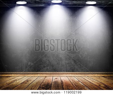 Black Grunge Wall With Three Lamps And Old Wooden Floor.