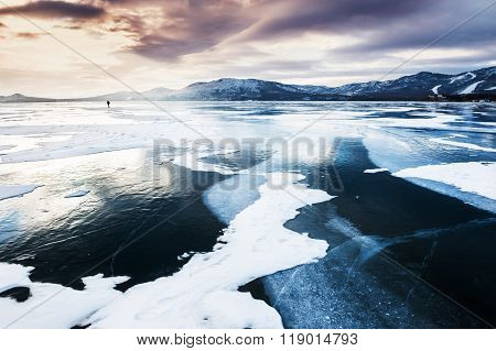 Frozen Lake And Mountains At Sunset.