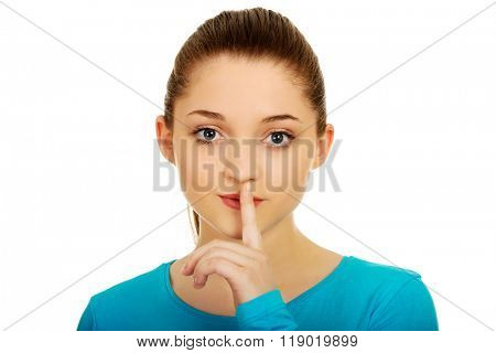 Teen woman with hush gesture.