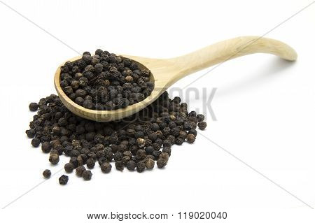 Black pepper and wooden spoon on white isolated background