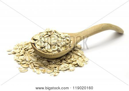 Rolled oats in wooden spoon on white isolated background