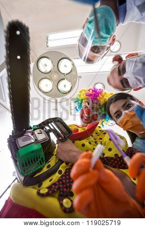 Nightmare delusion of dental operation with clown from horror holding chainsaw in bottom view