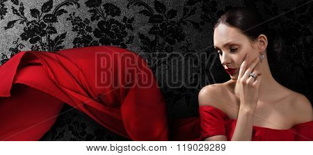 Beautiful woman in red evening dress on dark background. Banner.Space for text.