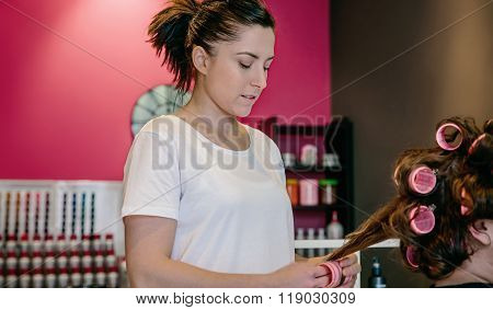 Hairdresser curling woman hair in a beauty salon