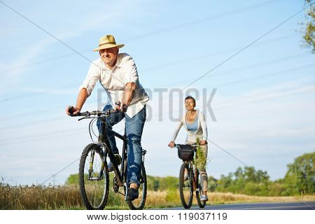 Senior couple cycling with bikes in nature in summer