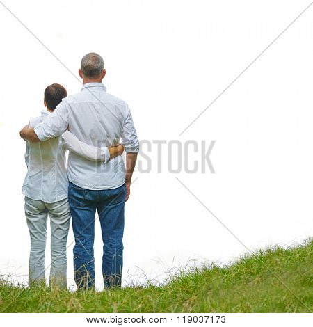 Back of old senior couple standing on a green hill