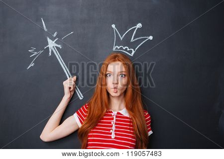 Playful funny young woman pretending fairy with crown and magic wand drawn on chalkboard background