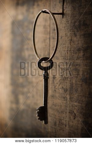 Solution concept image. Key hanging from wall. Key attached to ring hanging on a nail on a old grungy wooden wall.
