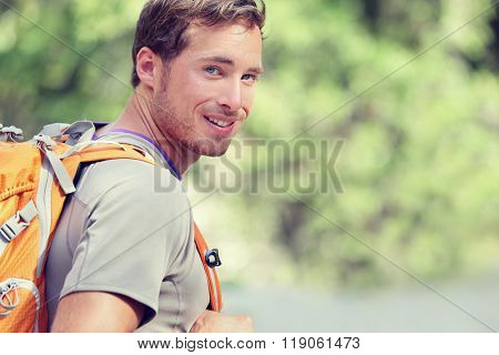 Young smiling backpack man in summer forest nature. Happy handsome male adult student looking at camera walking hiking in forest background. School bag or backpacking travel concept.
