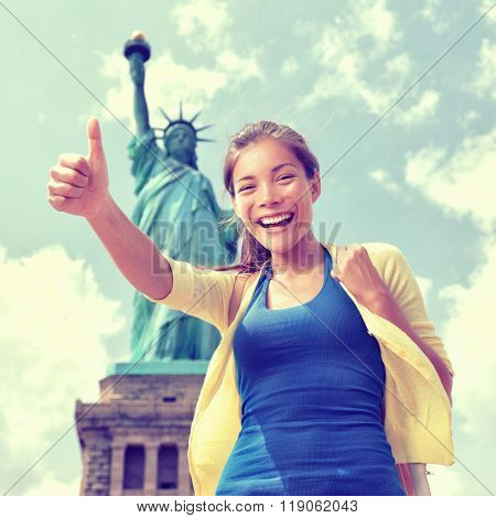 Happy Asian Chinese tourist doing thumbs up having fun visiting the Statue of Liberty, american landmark in New York City. Famous touristic attraction, USA.