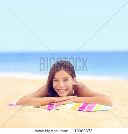 Happy vacation woman sunbathing relaxing on beach. Cute young Asian Caucasian ethnic mixed race girl lying down tanning under the sun on pastel towel on golden sand.