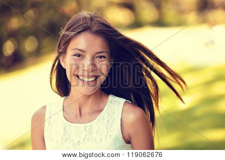 Confident young Asian Chinese beauty woman smiling. Beautiful portrait of healthy female adult in sunny summer grass park background for spring, summertime or pollen allergy season concept.