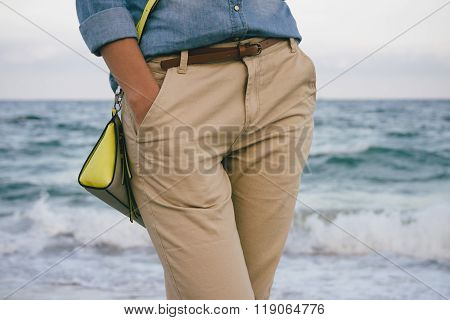 Woman In Denim Shirt And Beige Trousers Walking Along The Beach