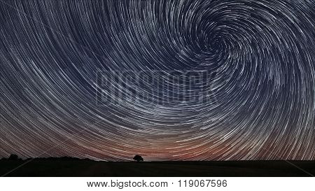 Beautiful Spiral Star Trails over filed with lonely tree. Beautiful night sky.