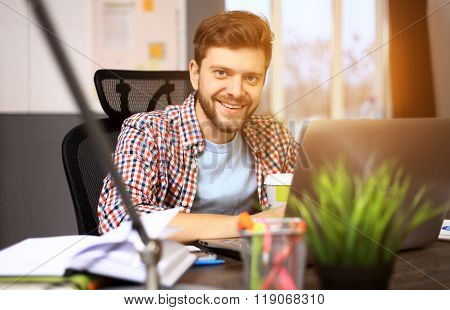Enjoying good working day. Confident young man working on laptop while sitting at his working place
