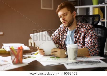 Thoughtful male person looking to the digital tablet screen while sitting in modern interior at the