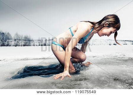 Young lady comes out from the ice hole after recreational swimming