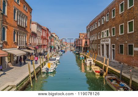 MURANO ITALY - 14TH MARCH 2015: A view along Fondamenta Dei Vetrai footpath in Murano during the day showing shops boats buildings and people