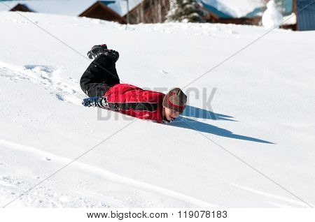 Adorable Boy Sliding Down Snow Hill On Body