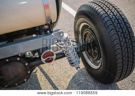 Rear view of old vintage customized hot rod car wheel and other parts