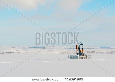Lone Pumpjack In Snowy Field