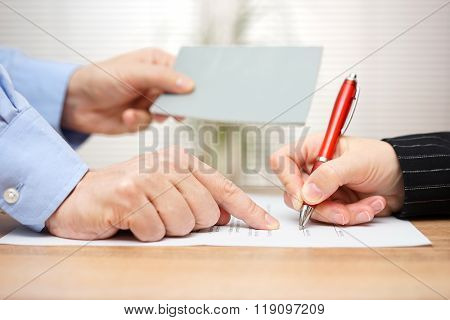 employer shows employee where to sign and giving her booklet at the same time