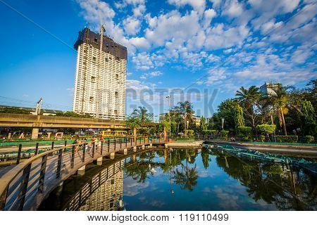Skyscraper And Walkway Along A Pond At Rizal Park, In Ermita, Manila, The Philippines.