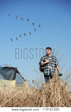 Young man camping while flock of geese fly in background