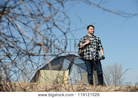 Millennial outdoorsman standing near tent during sunny day