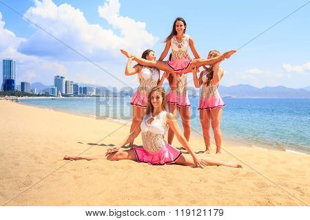 cheerleaders in white pink uniform perform Straddle Stunt one girl does split on sand beach against resort city poster