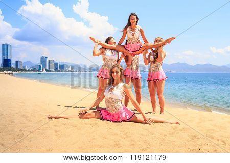 cheerleaders in white pink uniform perform Straddle Stunt one girl does split on sand beach against resort city poster