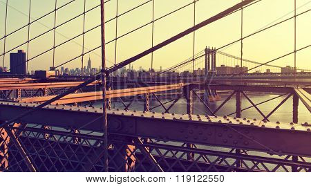 View of Empire State Building, Manhattan Bridge and Hazy City Skyline Through Support Cables and Past Girders of Historic Brooklyn Bridge at Warm Sunset, New York City, New York, USA