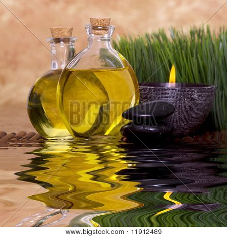 Relaxing candle and massage oil bottles front of green grass