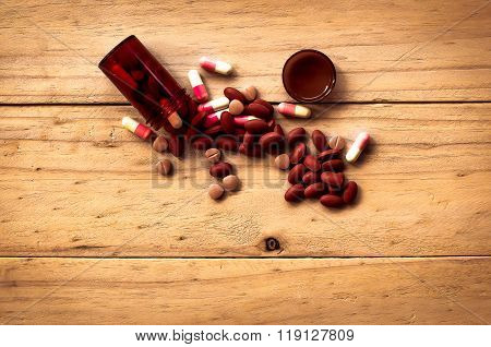 Pill Spilling Out Of Brown Color Pill Bottle On Old Wood Background