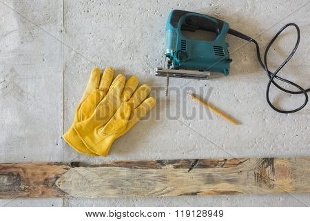 Electric jig saw and yellow gloves