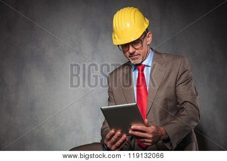 portrait of mature entrepreneur wearing helmet and glasses while seated, using his tablet in studio background