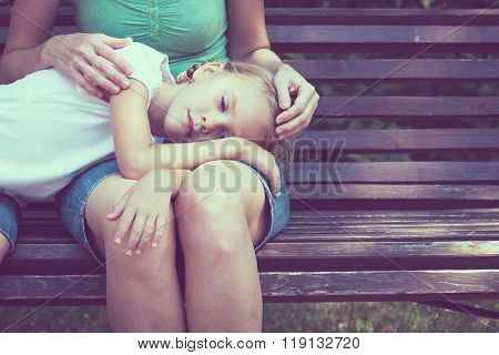 Sad Mother And Daughter Sitting On Bench In The Park
