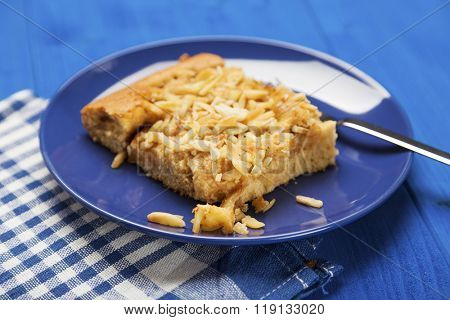 piece of homemade apple cake with almond slivers on blue plate, shallow depth of field