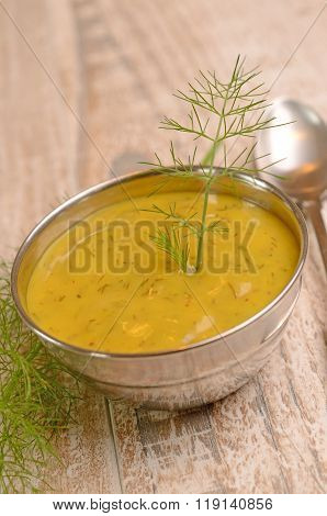 Dill sauce in a steel bowl on a wooden table, food background with view from above