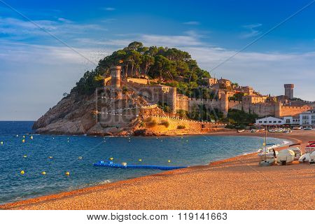 Fortress and fishing boats at Gran Platja beach and Badia de Tossa bay in the evening in Tossa de Mar on Costa Brava, Catalunya, Spain poster