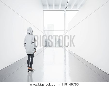 Photo of girl in empty contemporary gallery looking at the blank white canvas. Big windows, spotligh