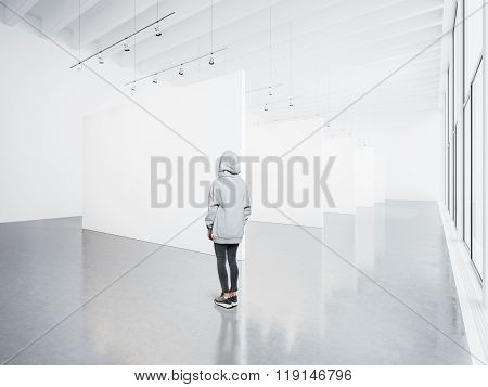 Photo of girl in empty modern gallery looking at the blank white canvas. Big windows, spotlights, co