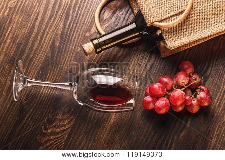 Glass With Wine, A Bottle And Bunch Of Grapes, Wooden Background