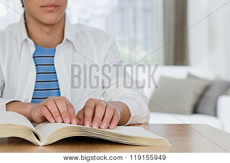 Blind boy reading a braille book