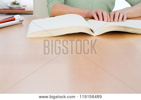 Woman reading a braille book