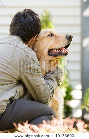Teenage boy hugging pet dog