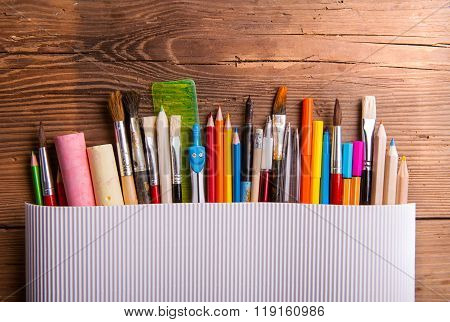 Various school and art supplies, wooden table, copy space